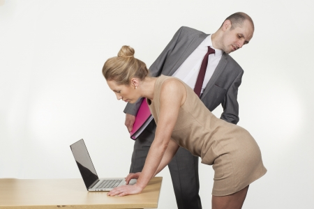 inappropriate: Sexual harassment by the boss in the workplace with a businessman bending over to ogle up under the skirt of a female colleague or secretary as she bends over a table to work on a laptop