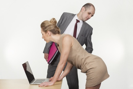 harassment: Sexual harassment by the boss in the workplace with a businessman bending over to ogle up under the skirt of a female colleague or secretary as she bends over a table to work on a laptop
