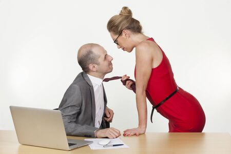 Seduction at the office as a sexy desirable businesswoman pulls on the end of the tie of a male colleague enticing him to get up from the desk and follow her