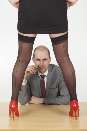 unsolicited: Image of a female assistant seducing her male boss by standing on top of the table and showing off her hot legs in office.