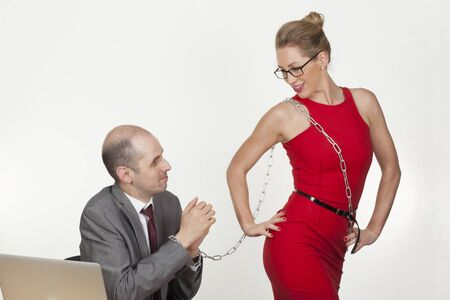 dominance: Sexual fantasies in the workplace with a provocative sexy female employee in a tight red dress holding a male coworker hostage with chained wrists in a play of dominance Stock Photo