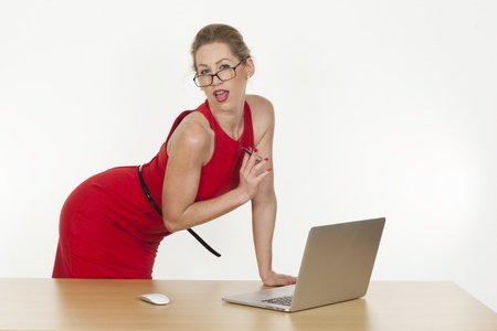 Image of a sexy assistant giving spicy pose wearing red dress at her desk in office photo