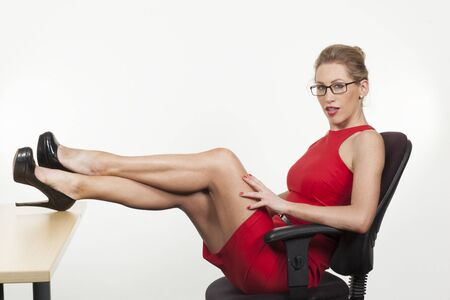 Sexy seducting secretary wearing a red dress and sitting with her feet on the desk photo