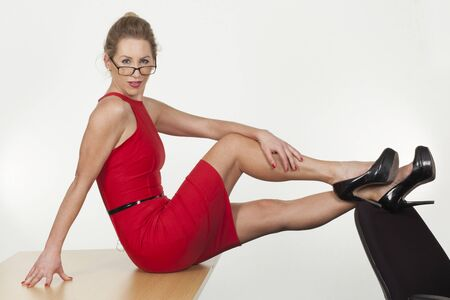 A provocative sexy businesswoman in glasses poses with her feet up on the back of a chair  photo