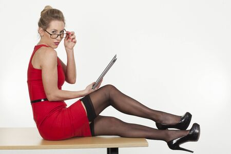 Beautiful sexy secretary sitting on top of the table  Stock Photo