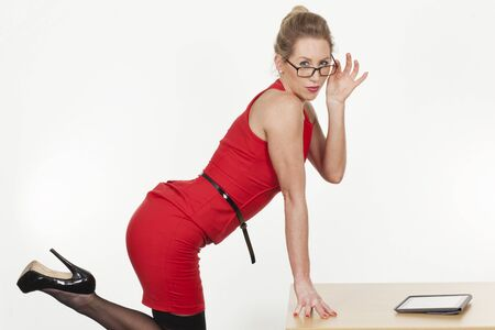 Sexy provocative businesswoman in a close fitting red dress kicking her stiletto in the air as she leans on a desk looking seductively over her glasses photo