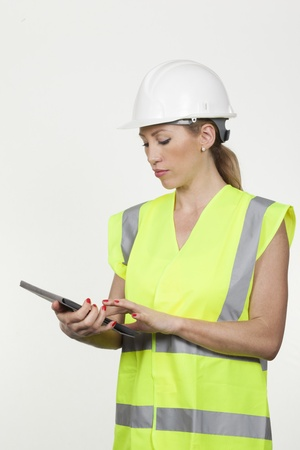 entering information: Female architect or engineer wearing a hardhat and high visibility fluorescent jacket entering information on a tablet computer