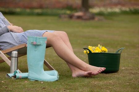 tomando refresco: Mujer que toma un descanso de trabajar en el jard�n y recoger narcisos en primavera se relaja en una silla en el c�sped con los pies desnudos extendidos y gumboots y una botella de refresco junto a su