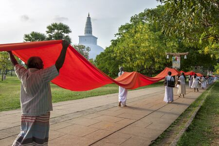 dagoba: Worshippers carry a ceremonial cloth towards the Ruwanwelisiya Dagoba at Anuradhapura in Sri Lanka.