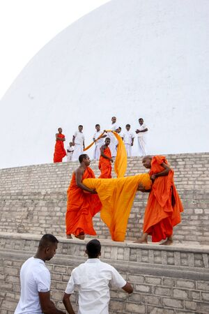 dagoba: Worshippers on a pilgrimage to Ruvanvelisaya Dagoba in Anuradhapura, Sri Lanka, assist monks in laying a giant orange cloth around the 292 metre circumference of the stupa. Editorial
