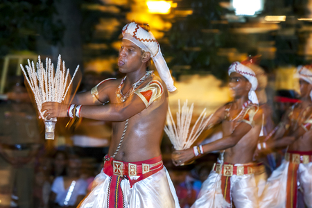 reciting: Coconut Flower Dancers perform on the streets of Kandy during the Esala Perahara in Sri Lanka. The Coconut flower is seen as a symbol of prosperity and the dancers perform in a vigorous manner whilst reciting verses and passing the coconut flower from han