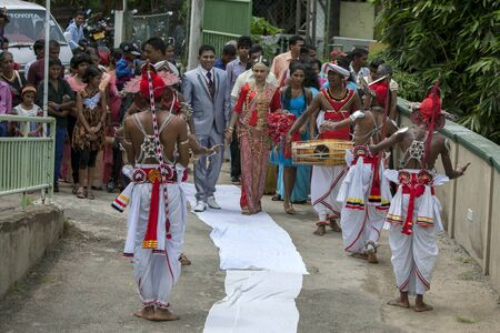 a newly married couple: A newly married couple walk down the white carpet towards their reception at Pinnewala whilst being entertained by traditional Sri Lankan drummers and dancers.