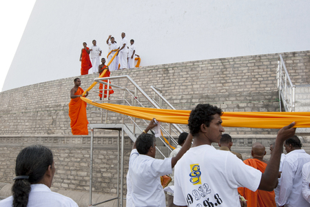 dagoba: Worshippers on a pilgrimage to Ruvanvelisaya Dagoba in Anuradhapura assist monks in laying a giant orange cloth around the 292 metre circumference of the stupa. Sri Lanka.