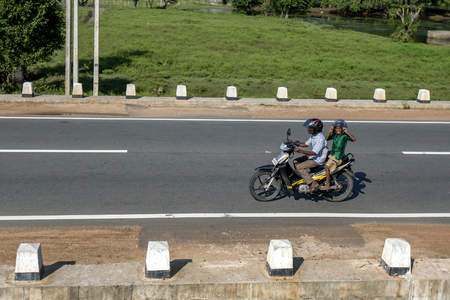 motor bike: A man rides his motor bike on the highway  north of Elephant Pass in Northern Sri Lanka. Editorial
