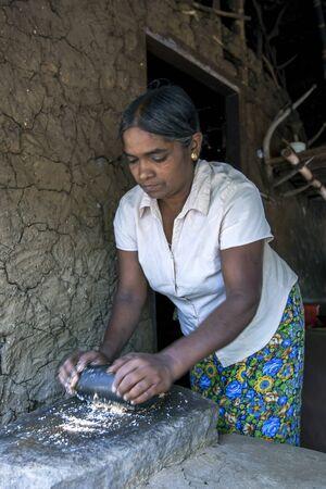 sigiriya: A lady grinds grain at her home using a stone in Sigiriya, Sri Lanka.