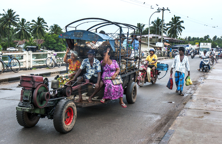 cart road: A mandrives his cart loaded with people and goods through Negombo in Sri Lanka,
