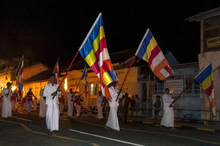 held down: Buddhist Flag Carriers walk in what is considered a solemn but spiritual manner down the streets of Kandy during the Esala Perahara in Sri Lanka.The Esala Perahera is held to honour the Sacred Tooth Relic of Lord Buddha which is enshrined within the Tem Editorial