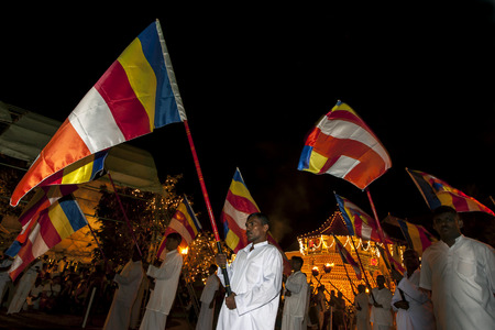 sri lankan flag: Buddhist Flag Carriers walk in what is considered a solemn but spiritual manner down the streets of Kandy during the Esala Perahara inSri Lanka.The Esala Perahera is held to honour the Sacred Tooth Relic of Lord Buddha which is enshrined within the Temp Editorial