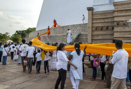 dagoba: Having carried an orange cloth around the Ruwanwelisiya Dagoba pilgrims then hand it to Buddhist monks who encircle the dagoba once more before tying the cloth to the base of the structure. Editorial