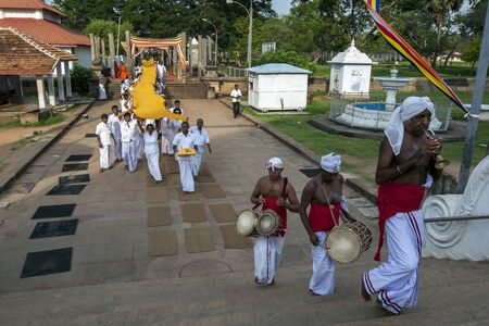 trumpet player: Pilgrims to Anuradhapura carry a 300 metre orange cloth towards the 2nd Century BC Ruwanwelisiya Dagoba.Sri Lanka. In the foregroung a Trumpet player and drummers lead the procession.
