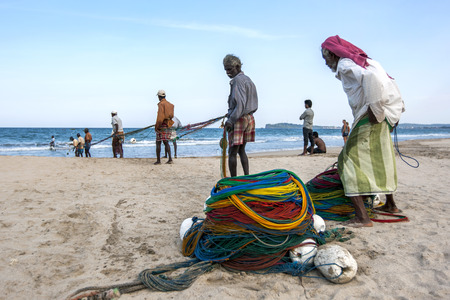 redes de pesca: Fishermen pull in their fishing nets on the beach at Uppuveli in Sri Lanka.