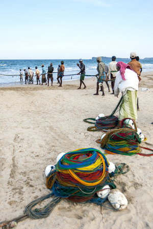 redes de pesca: Fishermen pull in their fishing nets on the beach at Upperveli in Sri Lanka.