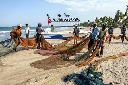 fishing nets: Fishermen pull in their fishing nets on the beach at Uppuveli in Sri Lanka.