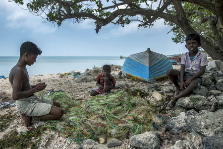 delft: Boys repair a fishing net on Delft Island in the northernSri Lankan region of Jaffna. Editorial