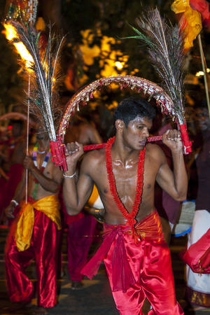 kavadi: A Kavadi Dancer performs through the streets of Kandy during the Esala Perahara in Sri Lanka. Kavadi Dancers are Hindu performers who also participate in the Buddhist Esala Perahera. The Esala Perahera runs every year in late July or early August for ten  Editorial