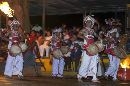 lord buddha: Thammattam Players perform in front of large crowds during the Esala Perahera in Kandy, Sri Lanka. The Esala Perahera is held to honour the Sacred Tooth Relic of Lord Buddha which is enshrined within the Temple of the Sacred Tooth Relic and is considered