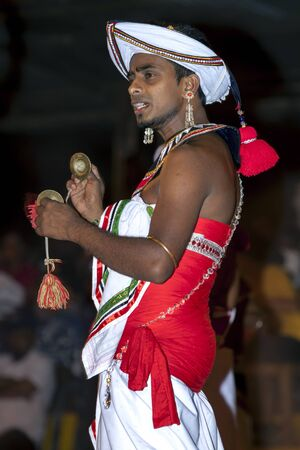 cymbal: A Cymbal Player Thalampotakaruwo perform in front of a large crowd gathered along the streets of Kandy during the Esala Perahara in Sri Lanka. Editorial