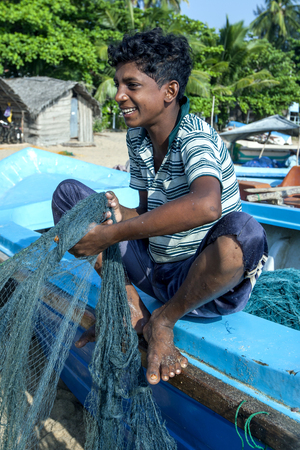 untangle: A young fisherman helps to untangle nets after a nights fishing off Arugam Bay on the east coast of Sri Lanka.