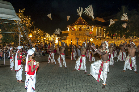 reciting: Coconut Flower Dancers perform infront of the Temple of the Sacred Tooth Relic during the Esala Perahera, Kandy, Sri Lanka. The Coconut flower is seen as a symbol of prosperity and the dancers perform in a vigorous manner whilst reciting verses and passin Editorial