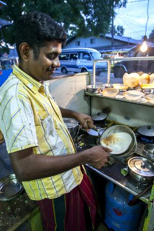 sri lanka temple: A man cooking hoppers in his restaurant near the Kataragama Temple in Sri Lanka.