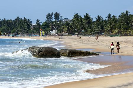 Surfers walk past Seven Star Rock at Arugam Bay on the east coast of Sri Lanka. Editorial