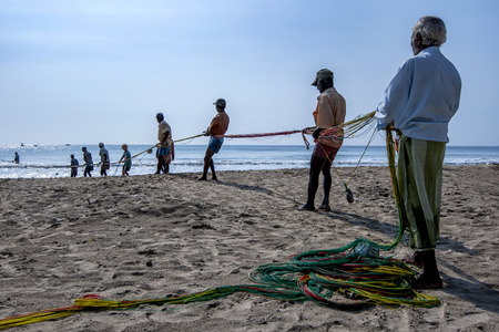 after hours: Fishermen hauling in their drag nets from off Uppuveli beach. After hours of hard work they eventually had little to show for all their efforts. East coast of Sri Lanka.