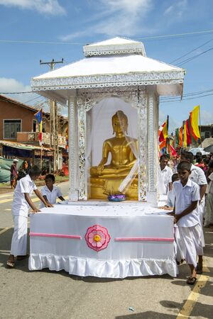 buddha sri lanka: A float carrying a statue of Lord Buddha is pushed through the streets during the Hikkaduwa Peraharaon the east coast of Sri Lanka. Editorial