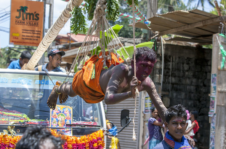 dozens: A Hindu man hangs from dozens of hooks piercing his body as a Hindu ceremony passes through the town of Mabawala in central Sri Lanka.