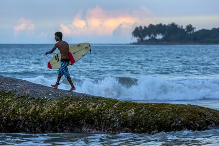 A surfer prepares to jump off Eight Star Rock to surf a beach break in the late afternoon at Arugan Bay in Sri Lanka.