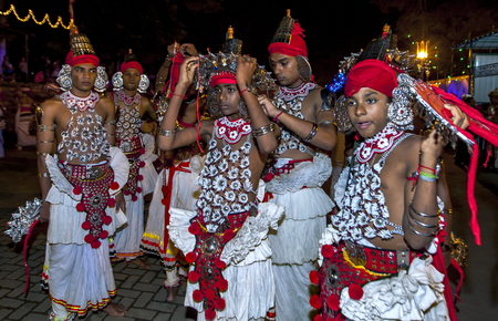 adjusted: A young Ves Dancer has his costume adjusted prior to the start of the Esala Perahera in Kandy, Sri Lanka.