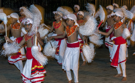 symbolically: Chamara Dancers perform along the streets of Kandy in Sri Lanka during the Esala Perahera. Chamara Dancers perform a dance whereby the yak tails they hold symbolically fan the Sacred Tooth Relic. The Esala Perahera is held to honour the Sacred Tooth Relic Editorial
