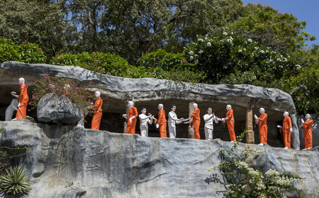 sri lanka temple: A line of Buddhist monk statues bearing gifts for Lord Buddha approaching the The Golden Temple at Dambulla, Sri Lanka.