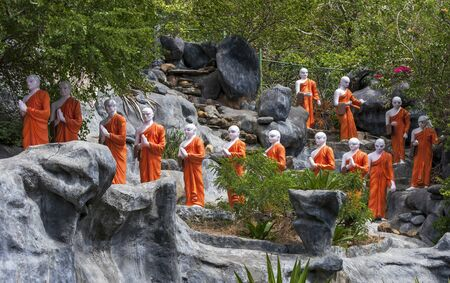 sri lanka temple: A line of Buddhist monk statues approaching the The Golden Temple at Dambulla, Sri Lanka.