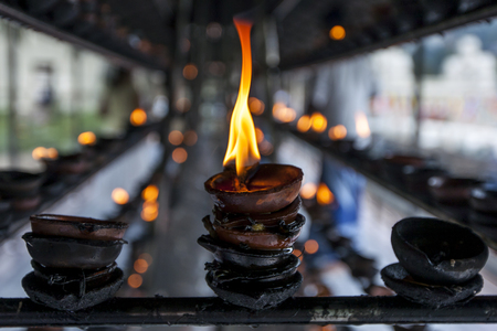 kandy: A flame burns in an oil cup at the Temple of the Sacred Tooth Relic, Kandy, Sri Lanka.