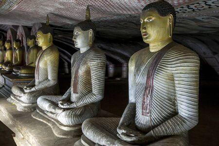 maharaja: A row of seated Buddha statues inside Cave 2 Maharaja Viharaya at the Dambulla Cave Temples in Sri Lanka.
