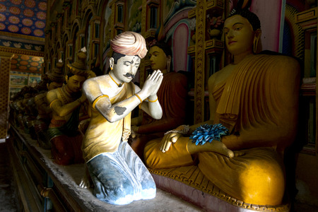 vihara: A ray of sunshine lights a statue worshipping Buddha in the Image House at Wewurukannala Vihara at Dickwella, Sri Lanka.
