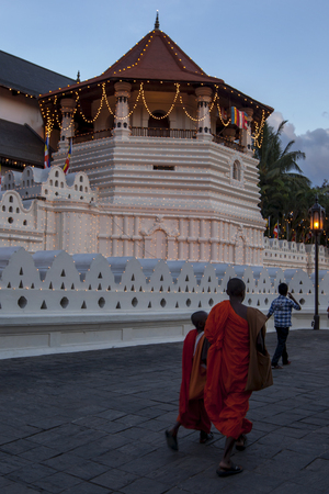 sri lanka temple: Buddhist monks walk past the Temple of the Sacred Tooth Relic in Kandy, Sri Lanka during the Esala Perahara. The Esala Perahera runs every year in late July or early August for ten days, ending on the Nikini poya full moon and is held to honour the Sacred