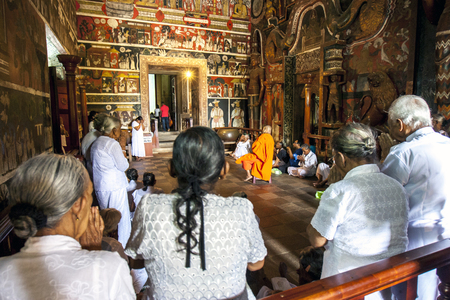 hallowed: A Buddhist monk holds court in the Image House at Kelaniya Raja Maha Vihara as pilgims pray. Buddhists believe the temple to be hallowed during the third and final visit of Lord Buddha to Sri Lanka, eight years after gaining enlightenment. This would make