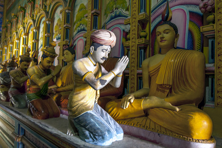 worshipping: A ray of sunshine lights a statue worshipping Buddha in the Image House at Wewurukannala Vihara at Dickwella in Sri Lanka.