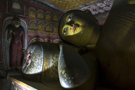 buddha sri lanka: A ray of light hits a reclining Buddha statue in Cave Three Maha Alut Viharaya at the Dambulla Cave Temples in Sri Lanka. Editorial
